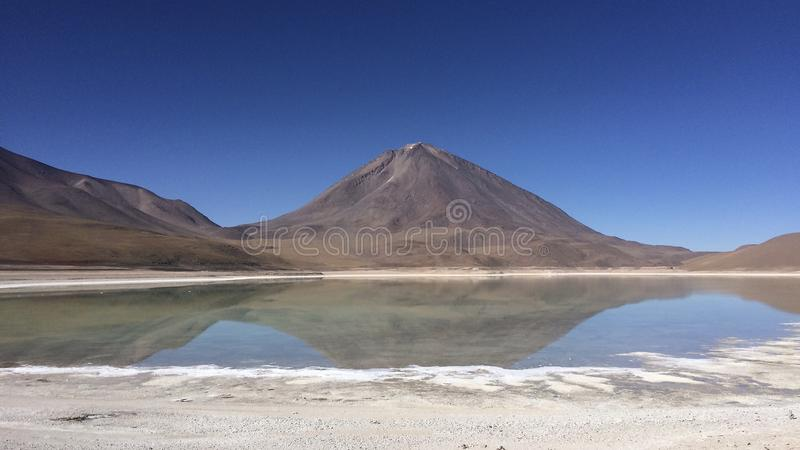 Volcano behind a clear lake in southern Bolivia stock image