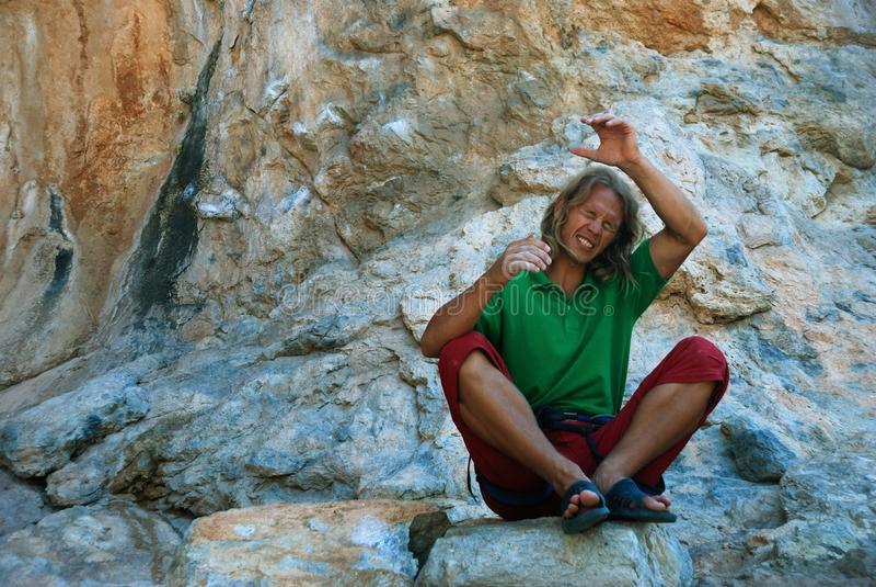 A young climber mentally climbs the rock stock photography