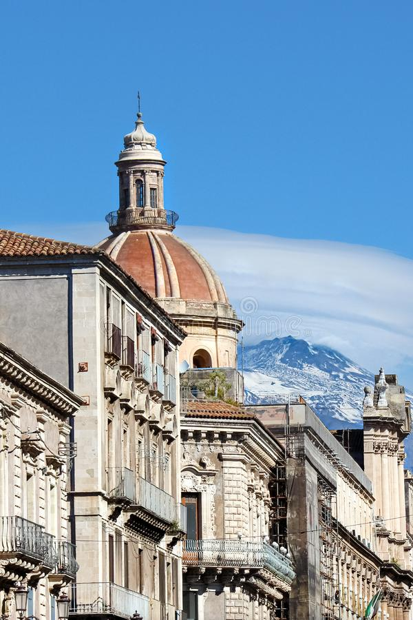 Beautiful close up photography of Catania Cathedral of Saint Agatha with adjacent historical buildings and Mount Etna. In the background. Snow on the very top royalty free stock photos