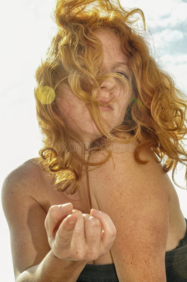 Beautiful close-up portrait of a young red-haired curly woman by the sea at the beach in Italy with bokeh circles royalty free stock photography