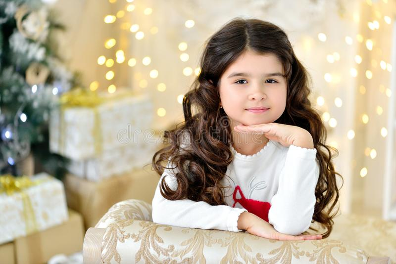 Beautiful close up portraite of curly girl with gold Christmas garlands magic lights and tree decorations gift box. Holiday, new year stock photography