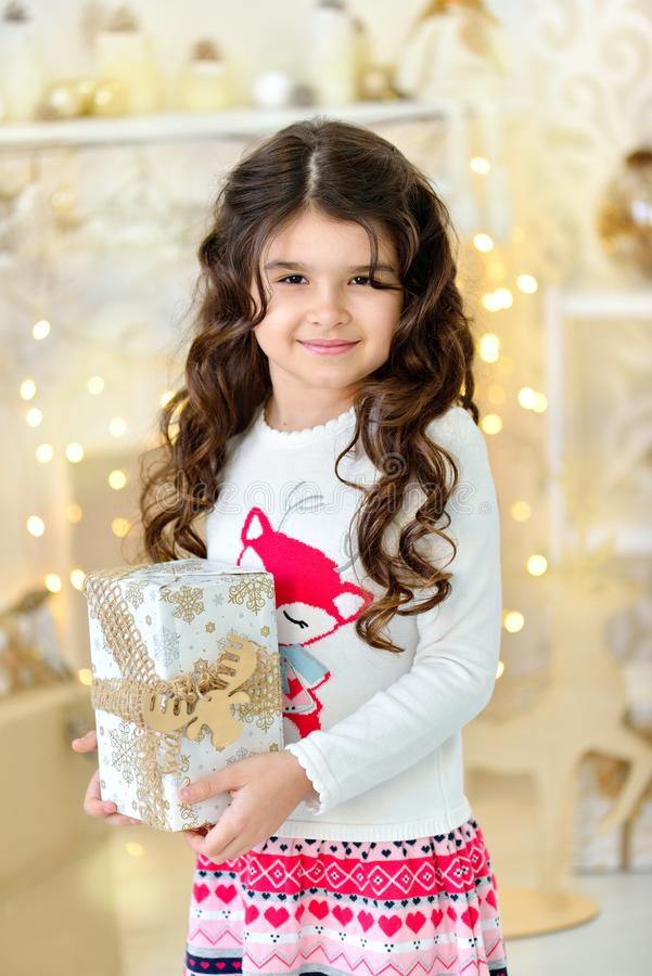 Beautiful close up portraite of curly girl with gold Christmas garlands magic lights and tree decorations gift box. Holiday, new year royalty free stock images