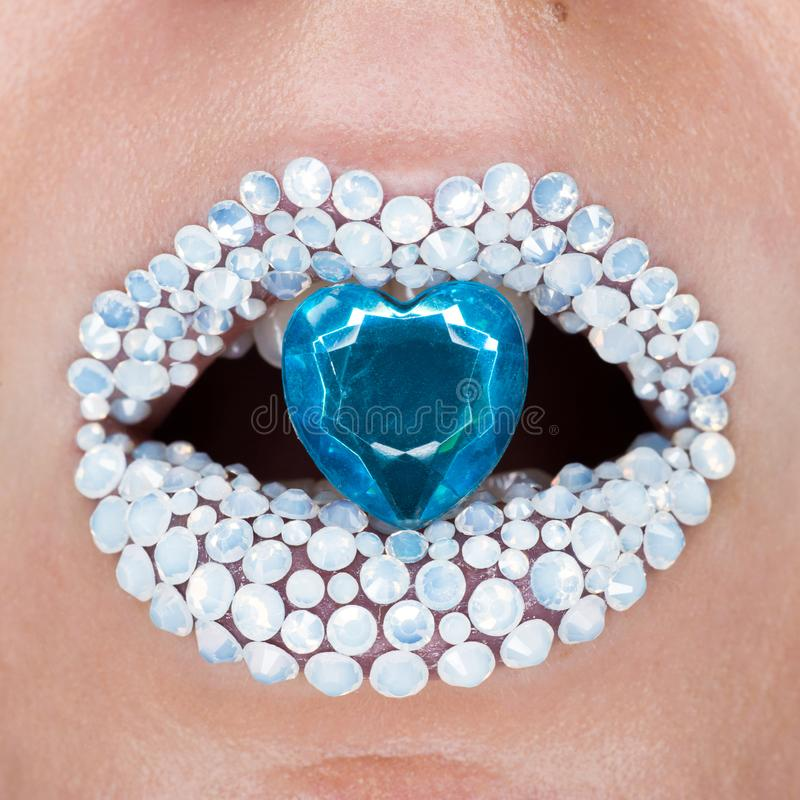 Beautiful closeup with female lips with white brilliants and blue brilliant in mouth. Make-up, glitter sparkles on lip royalty free stock photos