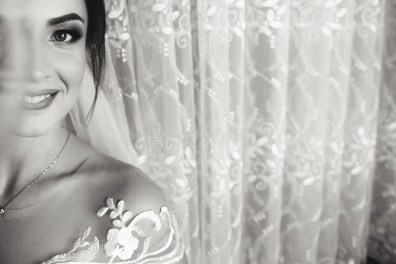 Beautiful closeup portrait of bride. Girl stand in luxury wedding dress near window. Black and white royalty free stock image