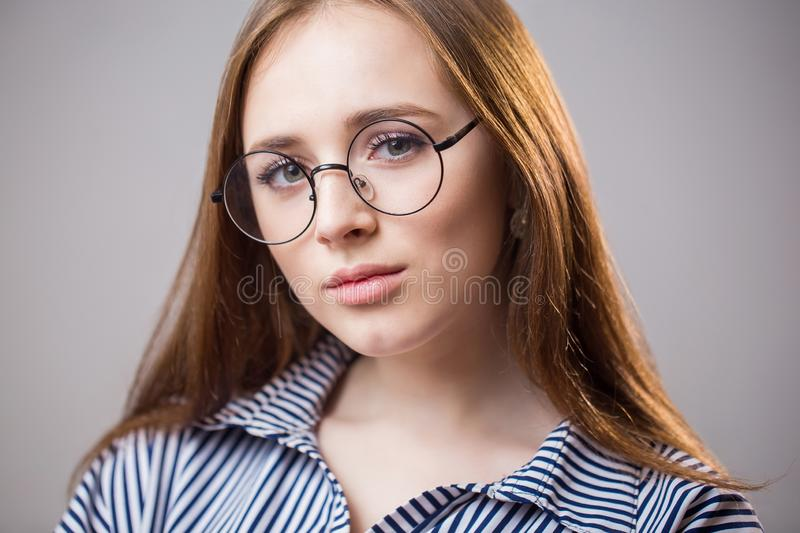 Beautiful closeup portrait of a young student girl wearing glasses on a gray background. Attractive redhead woman with natural royalty free stock photography