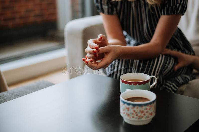 Beautiful closeup shot of two cups of tea on a black table and a female wearing a dress stock photography