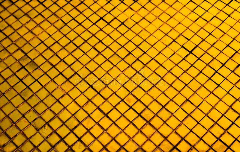 Beautiful closeup textures abstract tiles and black gold and yellow color glass pattern wall background and art wallpaper. S royalty free stock photos
