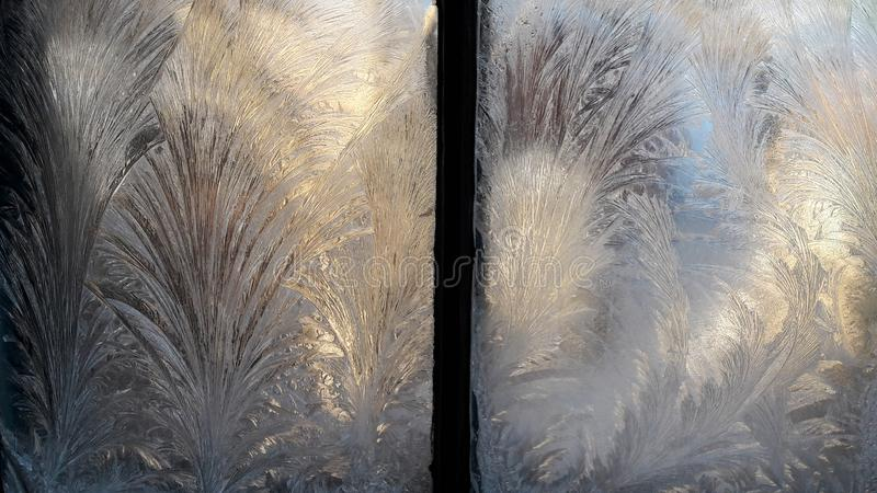 Beautiful Closeup Winter Window Pane Coated Shiny Icy Frost Patterns.. Frozen window glass, morning frost drawings on the window. Beautiful frosty patterns on stock images