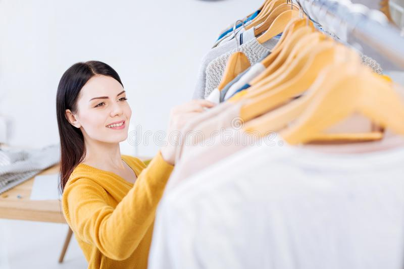 Positive young woman smiling while looking at the new clothes. Beautiful clothes. Cheerful emotional young worker of a fashionable atelier feeling satisfied with royalty free stock image