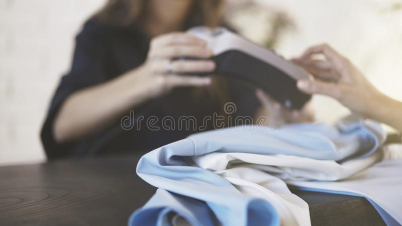 Beautiful clothes shop employee giving a card reader to a customer. Unrecognizable young shop assistant giving a card reader to a customer of a clothing shop royalty free stock photo