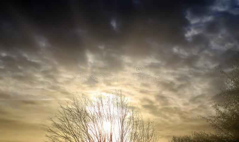 Beautiful cloud formations with sunlight beam shining in a sunset sky. Beautiful cloud formations with sunlight beam shining in a beautiful sunset sky royalty free stock images