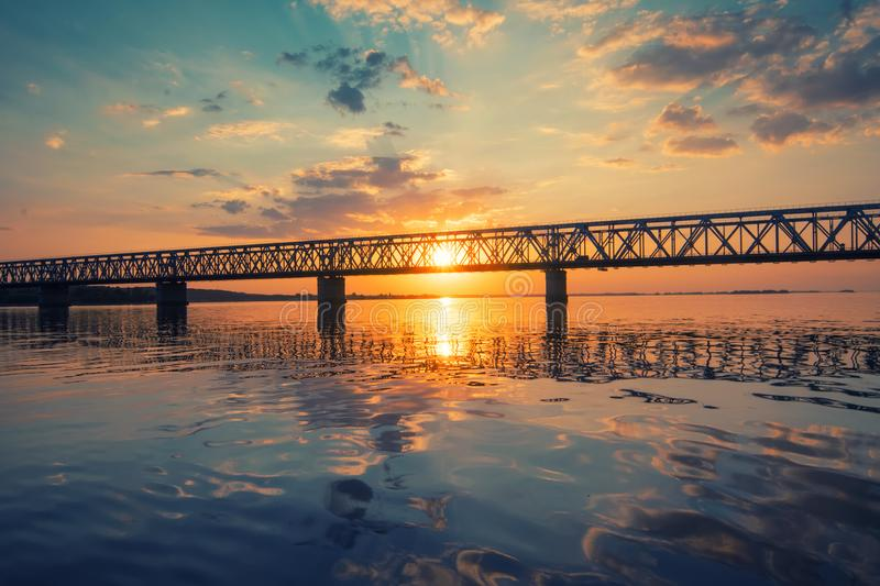 Amazing view to bridge across the Dnieper river, Cherkasy, Ukraine at sunset. Beautiful clouds and colorful water in river reflected in evening. Amazing sunset royalty free stock photography