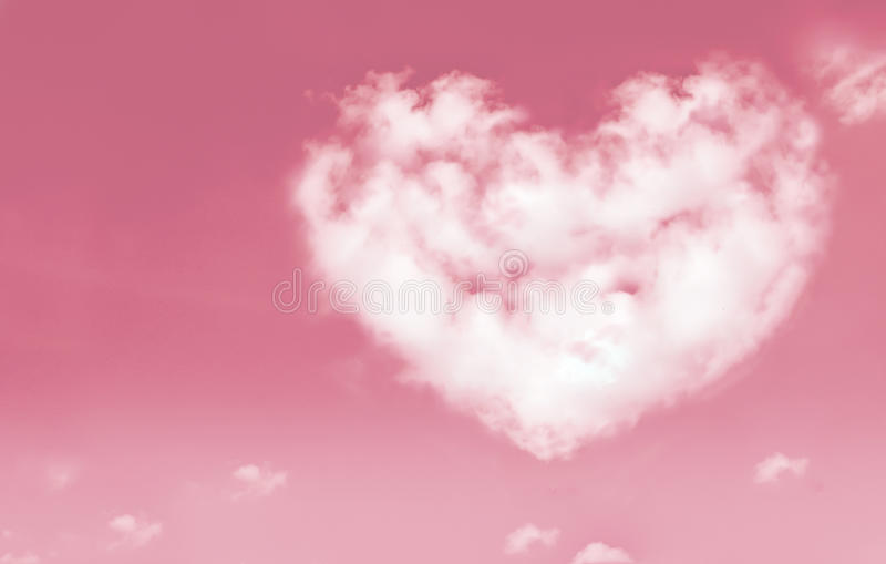 Beautiful clouds in heart shape on pink sky. Love and valentine stock photos