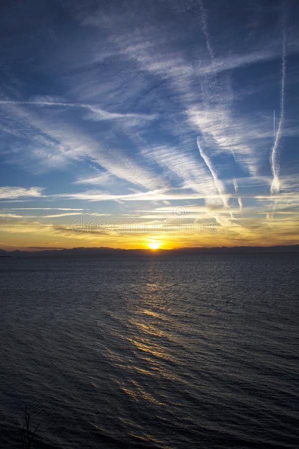 CLOUDS AND CONTRAILS IN THE SUNSET stock images