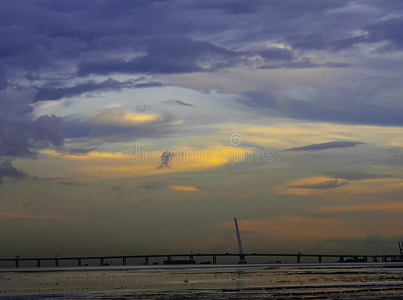 Beautiful clouds over bridge in the sky at dusk. Clouds in blue sky over bridge on the sea at dusk, landscape, seaview, water, city view in summer royalty free stock photos