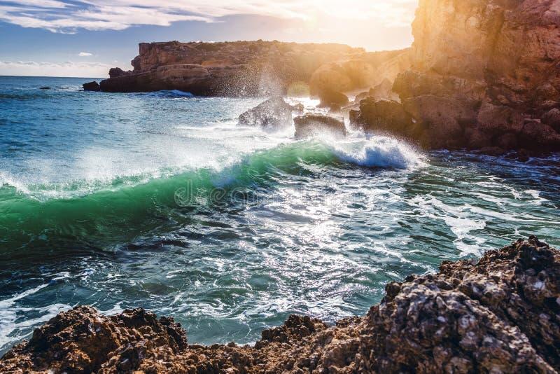 Beautiful coast of the ocean, Algarve, Portugal. Waves break against the rocks in the sun royalty free stock image