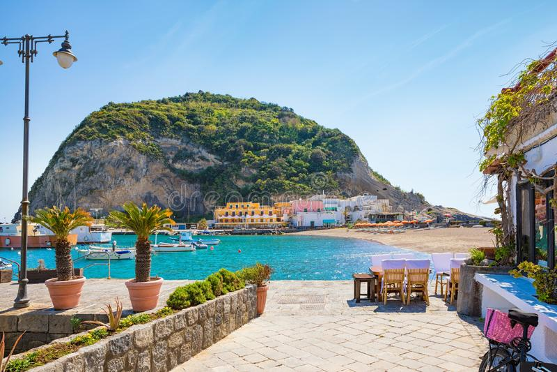 Beautiful coast of village Sant`Angelo, giant green rock in blue sea near Ischia Island, Italy. Sant`Angelo is small village within comune of Serrara Fontana stock photo