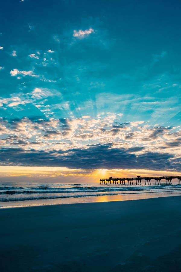 Beautiful ocean view at sunrise in Florida. Beautiful coastal scenery. Sun rising over horizon and pier, beach illuminated with sunlight, beautiful sky royalty free stock images
