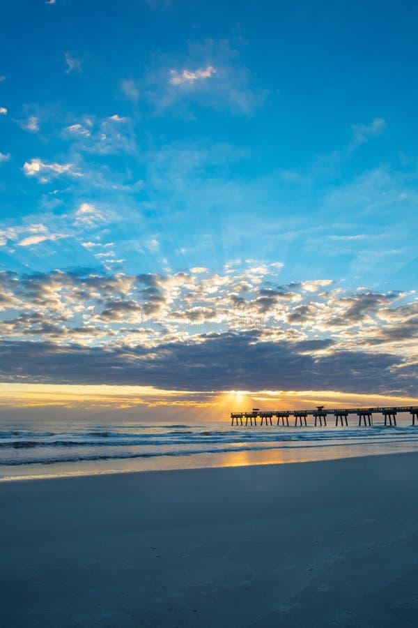 Beautiful sunrise on Florida beach. Beautiful coastal scenery. Sun rising over horizon and pier, beach illuminated with sunlight, beautiful sky reflected on the stock photo