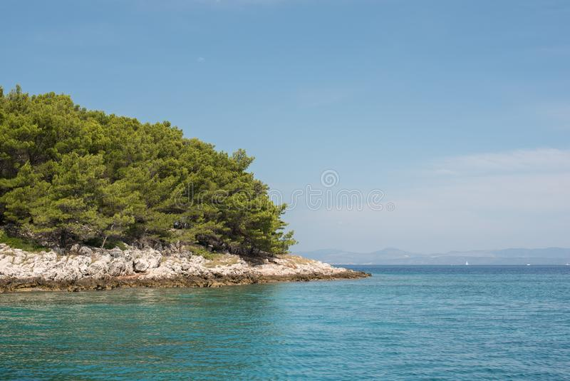 Beautiful coastline with green forest, stones and blue sky and sea water. Natural wallpaper. Adriatic coastline. Croatia. stock photos
