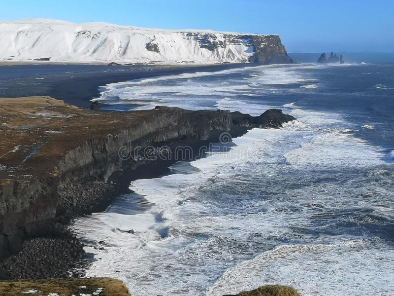 Black Sand coastline landscape in Iceland. Beautiful coastline scene with black sand and snowy mountain under a blue sky royalty free stock photos