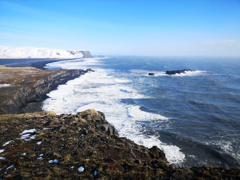 Black Sand coastline landscape in Iceland. Beautiful coastline scene with black sand and snowy mountain under a blue sky stock photos
