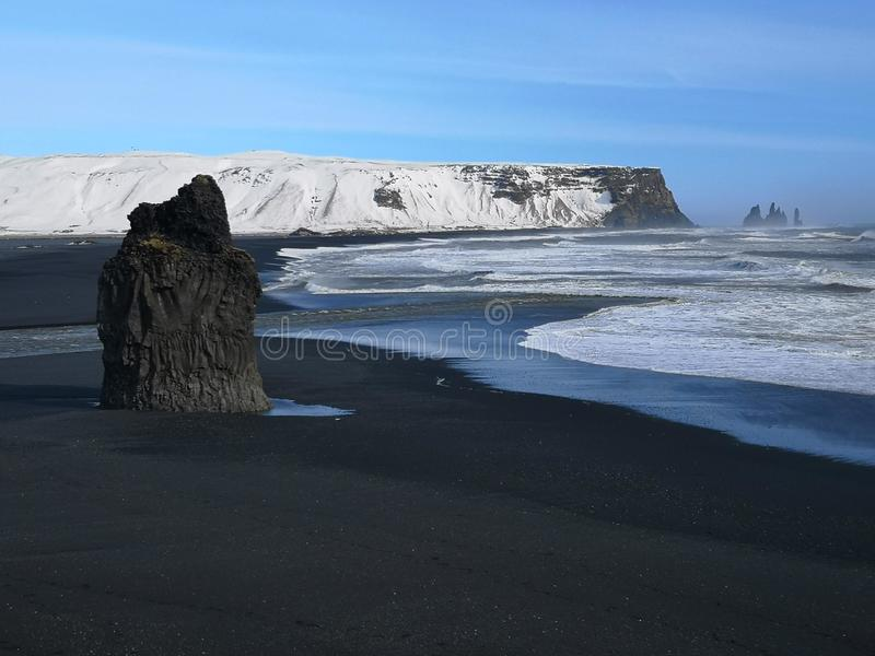 Black Sand coastline in Iceland. Beautiful coastline scene with black sand and snowy mountain under a blue sky royalty free stock image