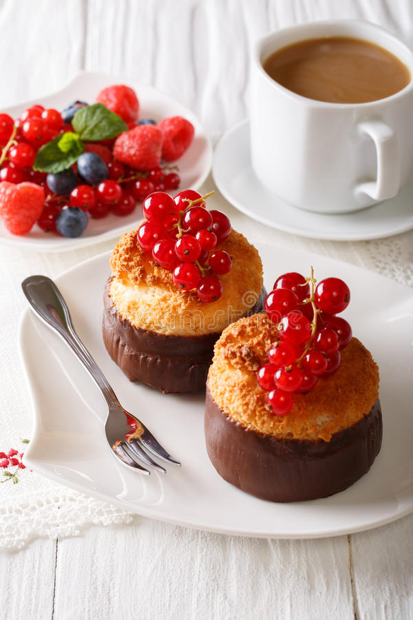 Beautiful coconut muffins with red currants and coffee close-up. royalty free stock image