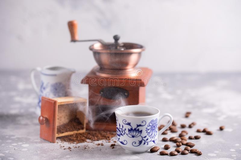 Grains of coffee fall out of a vintage coffee grinder. Hot black coffee in a beautiful porcelain cup on the table. A beautiful com. A beautiful coffee stock photos
