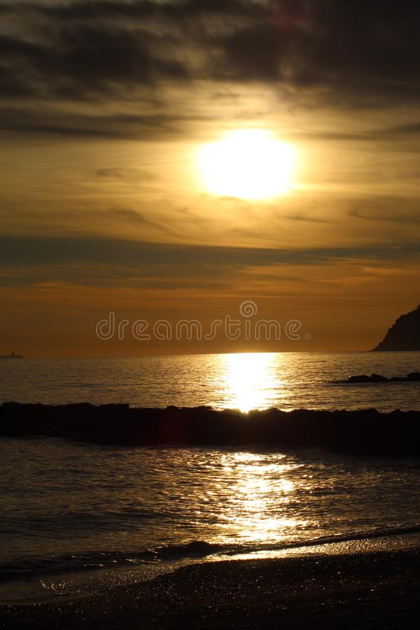 Sunset at the beach in Marinella di Sarzana. A beautiful cold afternoon in autumn at the beach in Italy. Looking at the sunset. The sun was slowly going down stock photos