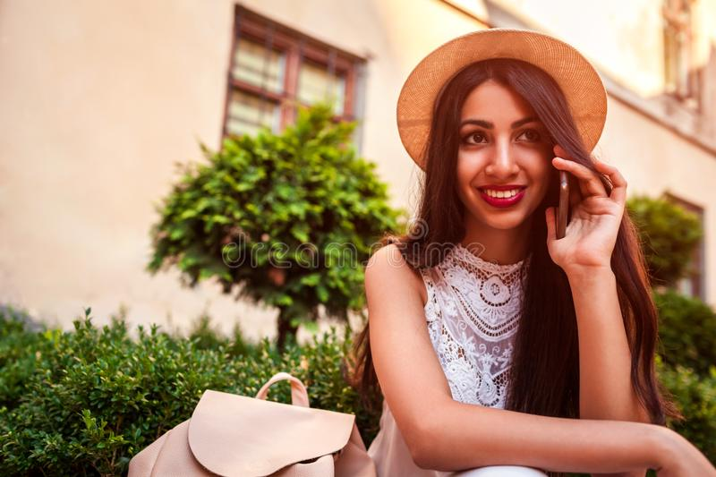 Beautiful college girl talking on phone outdoors. Middle eastern woman calling friends royalty free stock photo