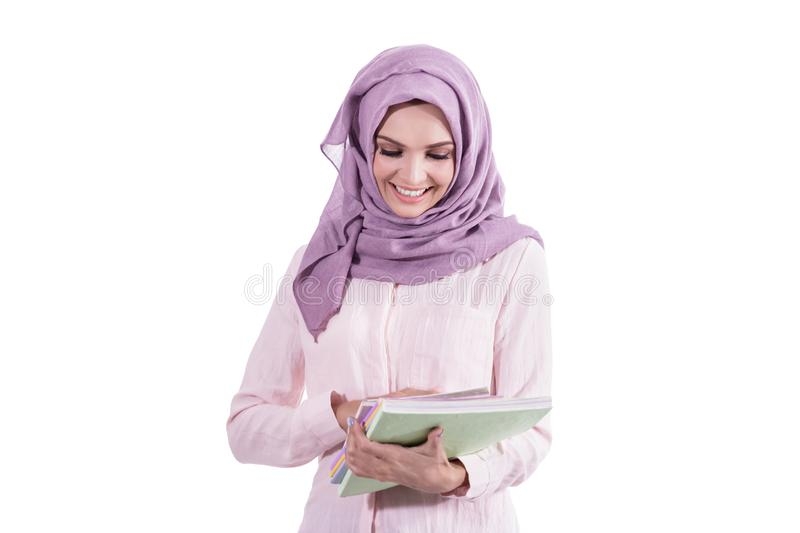 Beautiful college student wearing hijab holding some books royalty free stock image
