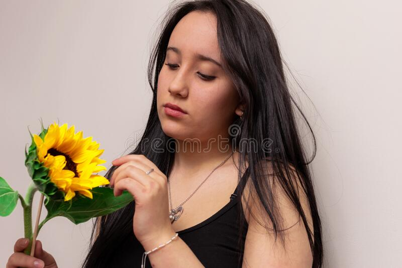 Beautiful Colombian teenage girl observes a pretty sunflower on Valentine`s Day. Young beautiful Colombian teenage girl observes a pretty sunflower on Valentine` stock photo