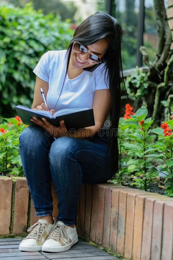 Beautiful Colombian woman with sunglasses sitting on a garden bench writing in her notebook and talking on cellphone royalty free stock images
