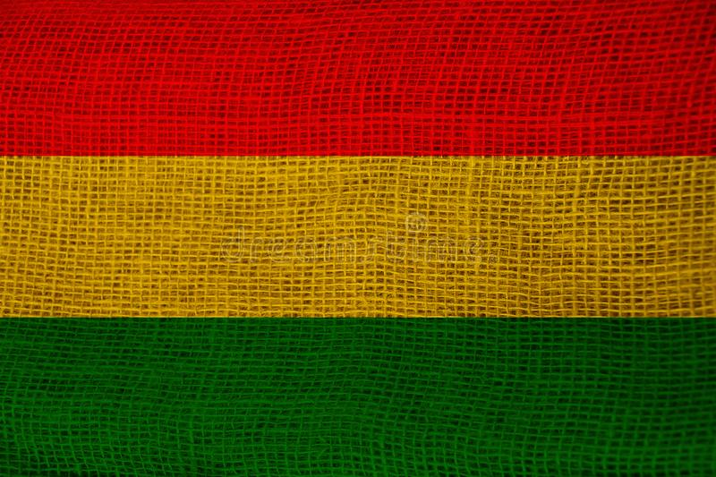 Beautiful colored national flag of bolivia state on fabric canvas, burlap, closeup, concept of tourism, economy and politics royalty free stock image