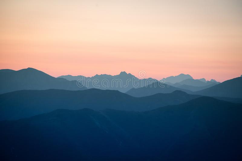 A beautiful, colorful, abstract mountain scenery in sunrise. Minimalist landscape of mountains in morning in blue tones. Tatra mounains in Slovakia, Europe stock image
