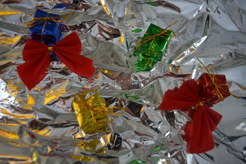 Beautiful multicolored New Year`s wrapped gifts with two red gift velvet on a silver, metallic background, crumpled paper. A beautiful colorful background stock image