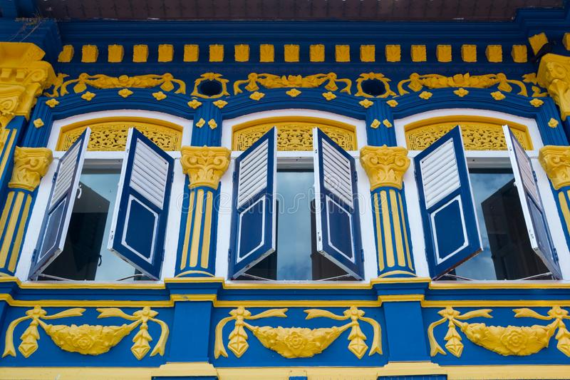 Beautiful colorful facade with open window shutters. Beautiful colorful facade with open window shutters. Beautiful Singapore. Beautiful colorful facade with royalty free stock image