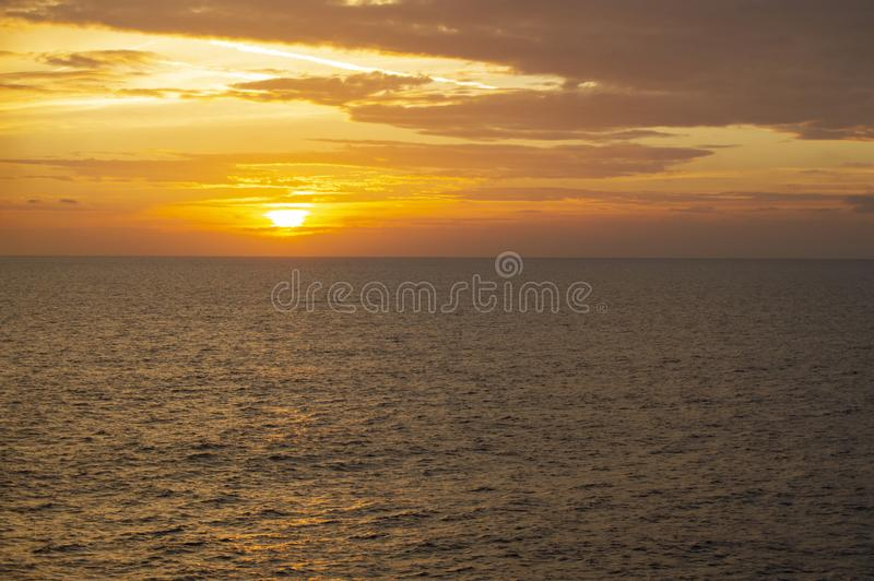 Beautiful colorful orange sunset on the sea with dark clouds and bright sun. Travel concept, sea cruises, outdoor background stock image