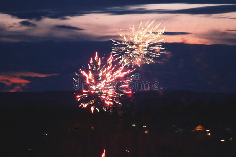 Beautiful, colorful patterns of light created in the dark night sky. Sparks from exploding fireworks scatter and fly in all royalty free stock images