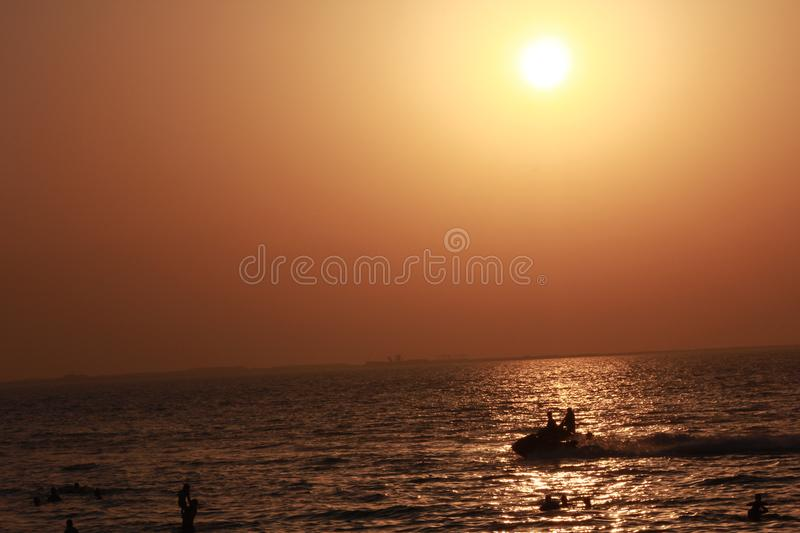 Beautiful colorful sea beach sunrise sunset colorful sky view people walking stock photo