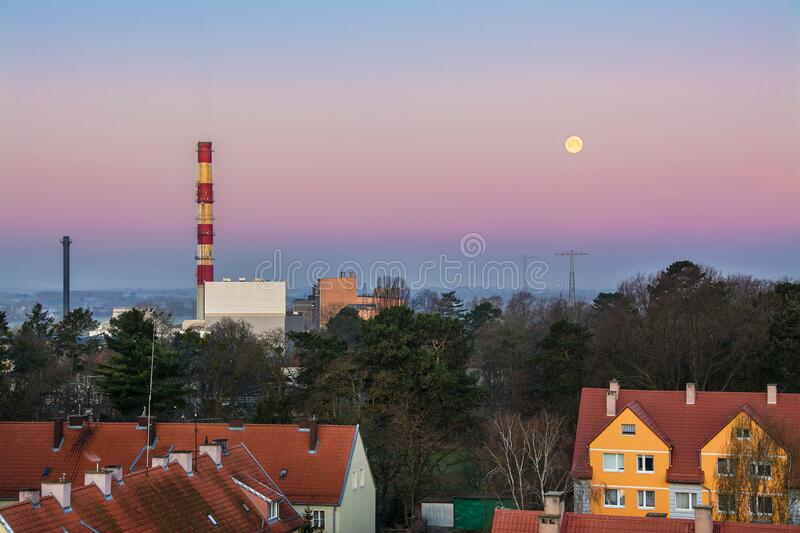 Beautiful colorful sky and moon, urban landscape, factory and houses. Elblag in Poland.  stock image