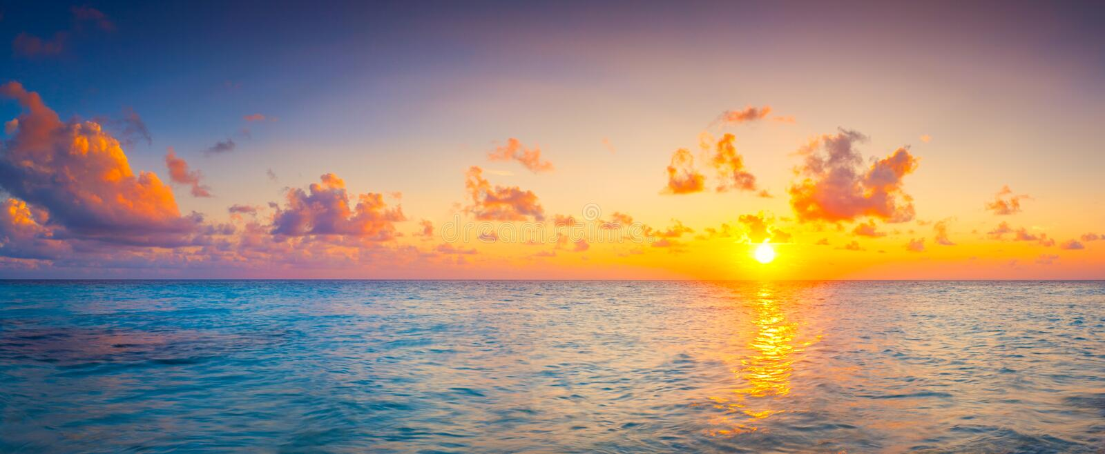 Beautiful colorful sunrise at the sea with dramatic clouds and sun shining in vintage style panorama.  royalty free stock photography