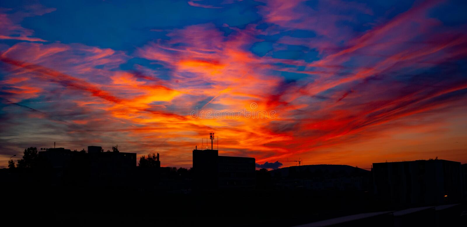 Beautiful colorful sunset with buildings silhouette. royalty free stock photography