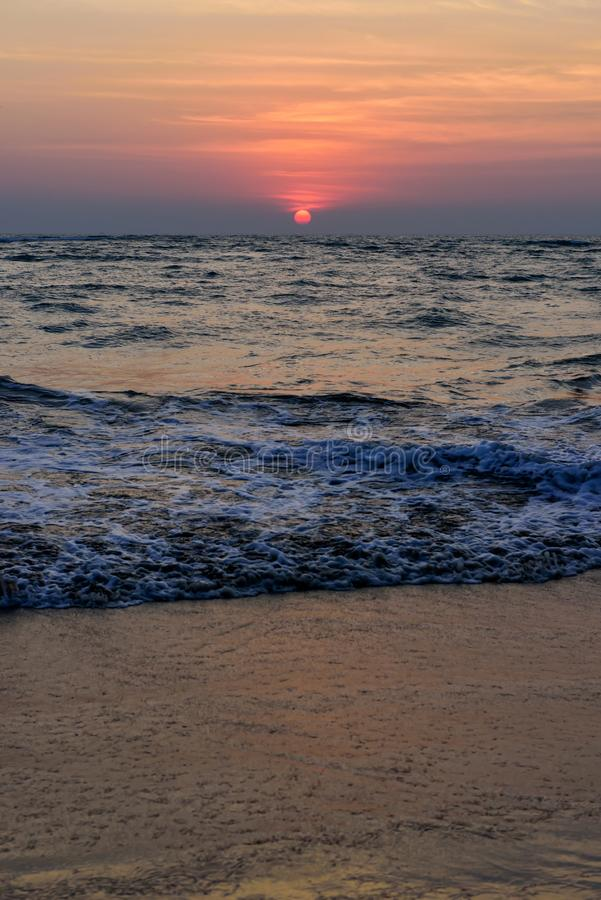Beautiful colorful sunset on the ocean, vertical photo. Sand beach, the sun sets in the clouds above the sea royalty free stock images