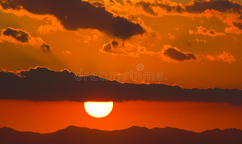 Beautiful and colorful sunset sky. The bright disk of the sun is partly hidden by the clouds stock image