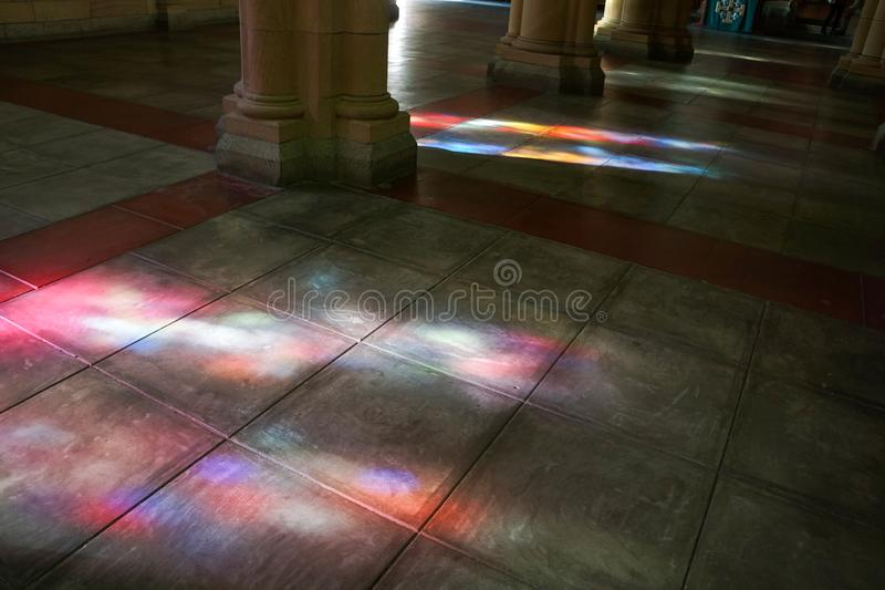 Coloured light by stained glass windows. Beautiful coloured light cast by stained glass church windows onto the flagstone floor. Negative space copy space stock photography