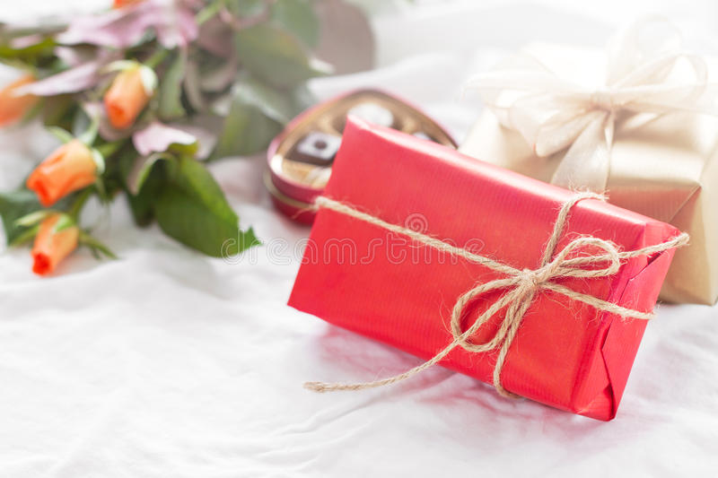 Beautiful colourful pretty gift or present in a natural paper wi. Th chocolate pralines, coffee and fresh roses on a bed. Holiday, valentine`s day or surprise stock photography