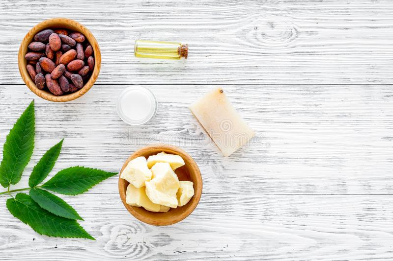 Beautiful composition with cocoa butter cosmetics. Cocoa butter and cocoa beans near homemade soap, cream, oil or lotion. In small bottles, green leaves on grey stock photography