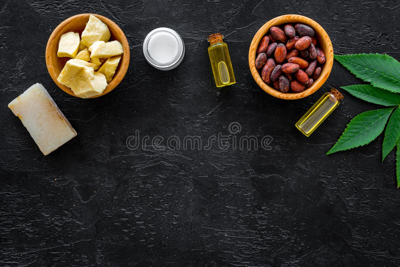 Beautiful composition with cocoa butter cosmetics. Cocoa butter and cocoa beans near homemade soap, moisturising cream. Oil or lotion in small bottles on black stock photography